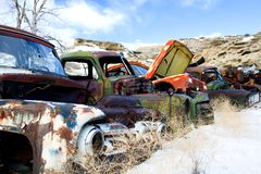 Old cars at junkyard. Old classic and vintage cars in the snow at a junkyard in rural Wyoming Royalty Free Stock Image