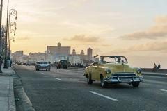 Old cars in Malecon, La Havana, Cuba. La Havana, Cuba December 25, 2016 Malecon typical view in sunset with La Havana buildings at background Stock Photos