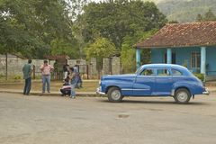 Old cars and three people in Cuban village in rural central Cuba Stock Images