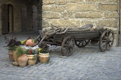 Old cart with firewood. Composition of the old cart with firewood and pots with flowers on the walls background. Evpatoria. Crimea. Ukraine Stock Image