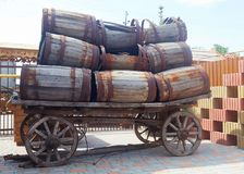 An old cart loaded with a lot of empty barrels. That need repair Royalty Free Stock Photography