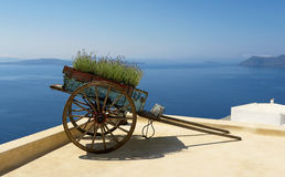 Old cart in Santorini. Old wooden cart in Santorini and panoramic view of the seascape royalty free stock photos