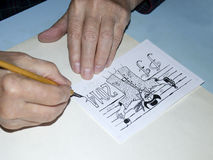 The old cartoonist hands drawing Stock Image