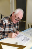 The old cartoonist at work. The old cartoonist is drawing the cartoons stock photo