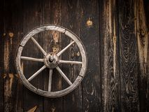 Old cartwheel hanging on a wooden barn stock image