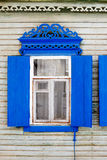 Old carved painted in blue wooden window in a wall Stock Images