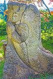 Old carved stone angel. Angel praying, carved on a rock in countryside in Summer, background trees and bushes stock image