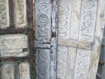 Old Carved Wooden Doors. Old weathered wood doors with decorative carved scroll design Royalty Free Stock Images