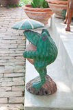 Old carved wooden frog on cement steps Royalty Free Stock Images