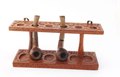 Old carved wooden pipe stand with pipes Royalty Free Stock Photography