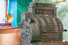 Old cash register and gramophone. Vintage decorated metal cash register in an old styled interior with gramophone on background Stock Photo