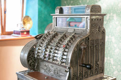 Old cash register and gramophone. Vintage decorated metal cash register in an old styled interior with gramophone on background Royalty Free Stock Images