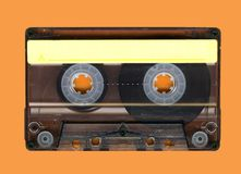Old cassette tape. Old Grungy cassette tape isolated over a orange background Royalty Free Stock Images