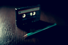 Old cassette tape. Old-fashioned cassette tape on the dark surface and green pencil stock photography