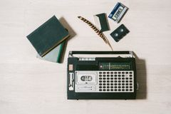 Old cassette tape recorder, books and feather. top view. Royalty Free Stock Photography