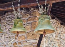 Old Brass Monastery Bells, Macedonia, Greece. Old cast brass Greek Orthodox monastery or church bells hanging by chains from a long roughly hewn timber beam royalty free stock photos