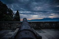Old cast canon overlooking sea shot in sunset royalty free stock photography