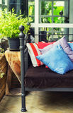 Old cast-iron bed with colorful pillows and wooden furniture Stock Photo