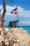 Old cast-iron cannon, and the ship anchor. In front of of the flag of the Dominican Republic on the Atlantic coast Stock Photography