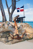 Old cast-iron cannon, and the ship anchor. In front of of the flag of the Dominican Republic on the Atlantic coast Stock Photo