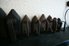 Old cast iron irons on a shelf in a junk shop royalty free stock image