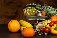 Old cast iron kitchen scale with fruit and vegetables. Healthy eating. Selling fruit. Royalty Free Stock Images