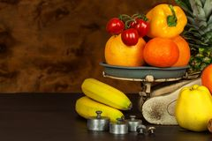 Old cast iron kitchen scale with fruit and vegetables. Healthy eating. Selling fruit. Stock Image