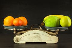 Old cast iron kitchen scale with fruit and vegetables. Healthy eating. Selling fruit. Royalty Free Stock Photo