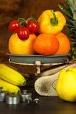 Old cast iron kitchen scale with fruit and vegetables. Healthy eating. Selling fruit. Stock Photos