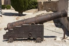 Old cast-iron Spanish cannon on a gun carriage from the ramparts. Royalty Free Stock Photography