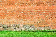 Old castle brick wall with green grass at the bottom Royalty Free Stock Images