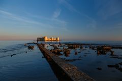 Old castle with bridge in the sea. Old castle in the sea with stones and bridge in Turkey at sunset Stock Photography