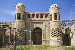 Old castle in Eastern Kazakhstan. Fortress the nomads. Walls and gate of the old fortress made of stone and lined with pattern. Ed tiles. Battle towers guarding Royalty Free Stock Image