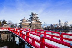Old castle in japan. Matsumoto castle against blue sky in Nagono city. Japan.Castle in Winter with heavy snowfall.Matsumoto Castle with frozen pond in Winter.a stock photography