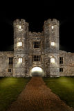 Old castle at night with lights and draw bridge. Old castle at night with lights shining through windows and draw bridge half down Stock Image