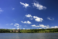 Old castle on the river bank. Old castle made of stone located near the river Stock Photo