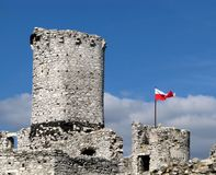 Old castle ruins. The old castle ruins of Ogrodzieniec fortifications, Poland. Polish flag above Royalty Free Stock Images