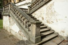 Old castle staircase and cracked walls. View of the old castle stone staircase with railing and flaked walls stock photography