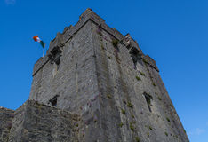Old castle tower with flying irish flag of Dunguaire Castle in Ireland Royalty Free Stock Photos