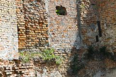 Old castle wall background. Uneven wall of an old abandoned castle. The hole in the ancient terrible building stock photography