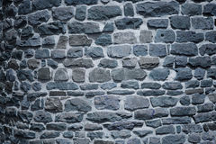 Old castle wall at night. Old castle wall background with irregular stone blocks at night royalty free stock image