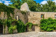 Old castle wall partially overgrown with plants and cobblestone courtyard royalty free stock photography
