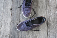 Old casual fade blue shoes with shoelace on wooden background Stock Photo