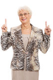An old casual lady pointing up on copy space. Stock Photos