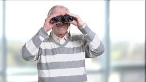 Old casual man with binoculars. Senior man using binoculars on blurred background. Serious grandfather with binoculars stock video footage