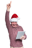 Old casual man with santa hat is winning while holding a tablet Royalty Free Stock Photos