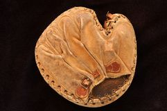 Old catchers mitt. Very old catchers mitt on black background Stock Images