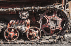 Rusty and dirty tracks and gearwheels of an old Tractor on the Scrapyard Stock Images