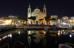 Old cathedral in a bay at early night. Old Maltese cathedral at early night with dark blue sky. Sea bay with boats around Stock Images