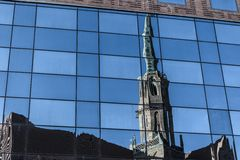 Old cathedral reflected on the glass building Stock Photos